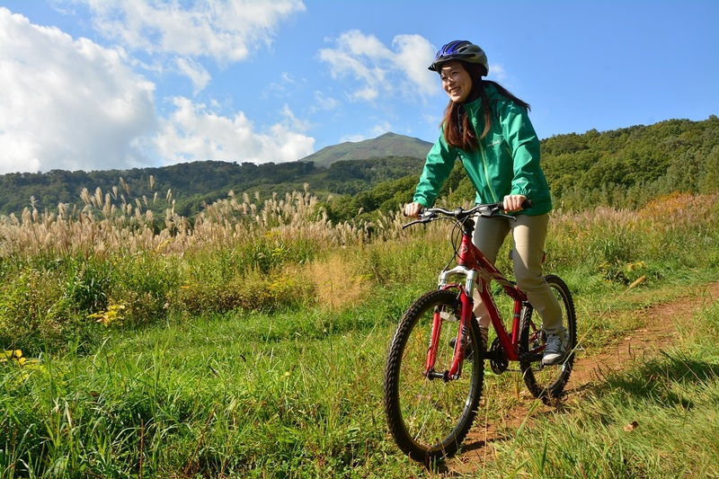 Girl riding mountain bike in summer Niseko